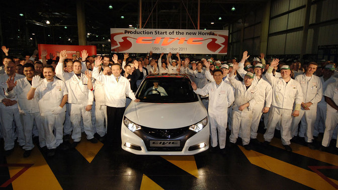 Soichiro Honda and some factory workers in white overalls.